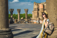 Stylish girl with backpack stand leaning on column. Travel, wanderlust concept. royalty free stock images