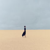 Stylish girl in black clothes walking in the desert.  Royalty Free Stock Photo