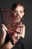 Stylish girl in a black dress with a fan Stock Photo