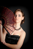 Stylish girl in a black dress with a fan Royalty Free Stock Photo