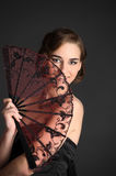 Stylish girl in a black dress with a fan Royalty Free Stock Images