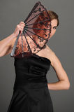 Stylish girl in a black dress with a fan Royalty Free Stock Image
