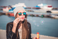 Stylish girl blowing soap bubbles. On the river bank Royalty Free Stock Image