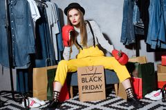 stylish girl in boxing gloves with shopping bags and clothes around, black stock photos