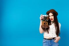 Stylish girl with camera. Blue background. Summer stock image