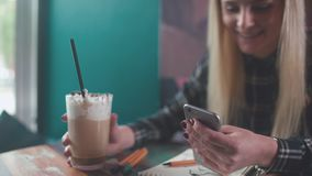 Stylish girl in a coffee shop, drink coffee, typing a sms. Stylish girl sits at a table in a coffee shop, drink coffee, typing a sms and smiles. Modern young stock video