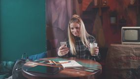 Stylish girl in a coffee shop, drink coffee, typing a sms and smiles. Stylish girl sits at a table in a coffee shop, drink coffee, typing a sms and smiles stock video footage