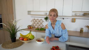 Stylish girl cooks posing for breakfast in morning, standing at table in modern bright kitchen in morning. stock video footage