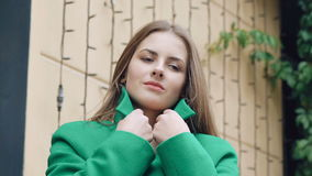 Stylish girl corrects green coat and smiling stock video footage