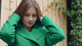 Stylish girl corrects green coat and smiling. Slowly stock video footage