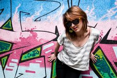 Stylish girl in a dance pose against graffiti wall Royalty Free Stock Photo