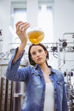 Stylish girl in denim jacket holding beaker of beer Royalty Free Stock Images