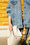 Stylish girl in a denim jacket in a hurry, waving a white square bag. Street lifestyle. royalty free stock images
