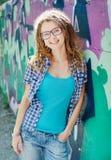 Stylish girl with dreadlocks, background wall with graffiti. Stock Photos