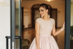 Stylish girl in dress stand in hotel hall. Girl smile to camera stock photo