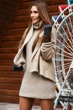 Stylish girl dressed in beige knitted dress, short sheepskin coat and gloves walks in the park on the sunny day royalty free stock photography
