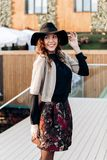Stylish girl dressed in a black turtleneck, beige cape, stylish short skirt and black hat with wide bells poses in the stock photography