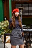 Stylish girl dressed in a gray turtleneck and orange beret poses outside royalty free stock images