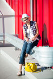 Stylish girl in jeans and hat sitting on street and reading book Royalty Free Stock Photos