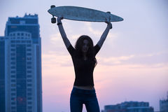 Stylish girl in jeans holding aloft longboard Royalty Free Stock Images