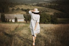 Stylish girl in linen dress and hat running barefoot in grass in sunny field at village. Boho woman relaxing in countryside,. Simple rustic life. Atmospheric royalty free stock photo