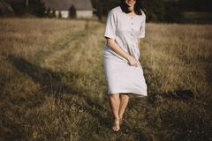 Stylish girl in linen dress and hat running barefoot in grass in sunny field at village. Boho woman relaxing in countryside,. Simple rustic life. Atmospheric stock photo