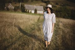 Stylish girl in linen dress and hat walking barefoot in grass in sunny field at village. Boho woman relaxing in countryside,. Simple rustic life. Atmospheric royalty free stock photo