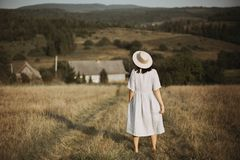 Stylish girl in linen dress and hat walking barefoot in grass in sunny field at village. Boho woman relaxing in countryside,. Simple rustic life. Atmospheric stock photos