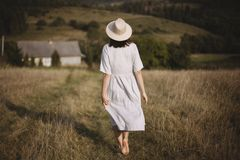 Stylish girl in linen dress and hat walking barefoot in grass in sunny field at village. Boho woman relaxing in countryside,. Simple rustic life. Atmospheric stock image