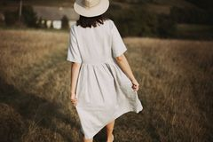 Stylish girl in linen dress and hat walking barefoot among herbs and wildflowers in sunny field in mountains. Boho woman relaxing. In countryside, simple rustic stock image
