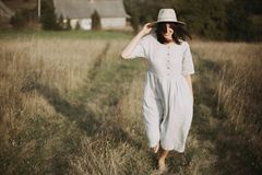Stylish girl in linen dress and hat walking barefoot among herbs and wildflowers in sunny field in mountains. Boho woman smiling. In countryside, simple rustic stock photos