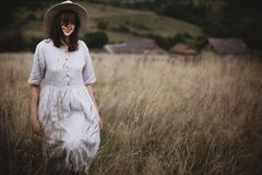 Stylish girl in linen dress and hat walking among herbs and wildflowers in field. Boho woman enjoying day in countryside, simple stock image