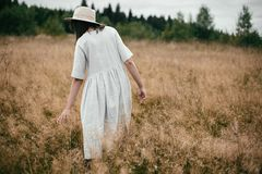 Stylish girl in linen dress and hat walking among herbs and wildflowers in field. Boho woman relaxing in countryside, simple slow stock photography