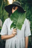 Stylish girl in linen dress holding big green leaf at face at wooden fence and grass. Portrait of boho woman in hat posing with. Leaf in summer countryside in stock photos