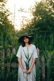 Stylish girl in linen dress holding green leaf at wooden fence and grass. Portrait of boho woman in hat posing with cane branch in. Summer countryside in royalty free stock image