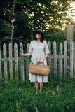 Stylish girl in linen dress holding rustic straw basket with green leaf at wooden fence and grass. Boho woman in hat posing in. Summer countryside in evening stock photos