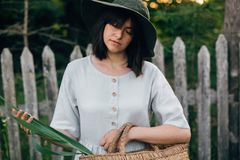 Stylish girl in linen dress holding rustic straw basket with green leaf at wooden fence and grass. Portrait of boho woman in hat. Posing in summer countryside stock image