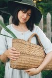 Stylish girl in linen dress holding rustic straw basket with green leaf at wooden fence and grass. Portrait of boho woman in hat. Posing in summer countryside royalty free stock photos