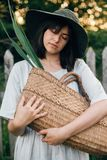 Stylish girl in linen dress holding rustic straw basket with green leaf at wooden fence and grass. Portrait of boho woman in hat. Posing in summer countryside stock photos