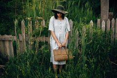 Stylish girl in linen dress holding rustic straw basket at wooden fence among green cane. Boho woman in hat relaxing and posing in. Summer countryside in royalty free stock photography