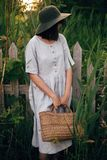 Stylish girl in linen dress holding rustic straw basket at wooden fence among green cane. Boho woman in hat relaxing and posing in. Summer countryside in stock photo