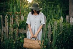 Stylish girl in linen dress holding rustic straw basket at wooden fence among green cane. Boho woman in hat relaxing and posing in. Summer countryside in stock images