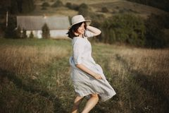 Stylish girl in linen dress running barefoot among herbs and wildflowers in sunny field in mountains. Boho woman relaxing in. Countryside, simple rustic life royalty free stock photo