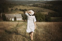 Stylish girl in linen dress running barefoot among herbs and wildflowers in sunny field in mountains. Boho woman relaxing in. Countryside, simple rustic life stock images