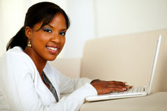 Stylish girl looking at you working on laptop Royalty Free Stock Image