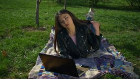 Stylish girl lying on lawn typing at laptop in park stock footage