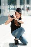 Stylish girl  photographs with the digital camera. Royalty Free Stock Photos