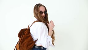 Fashion of modern youth. stylish girl posing against white wall in jeans, white shirt, with leather backpack and glasses. Stylish girl posing against white wall stock video footage