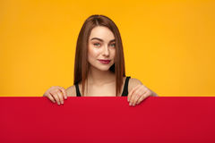 Stylish girl posing behind red cardboard stock photo