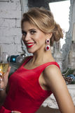 Stylish Girl in red party dress with champagne Royalty Free Stock Photography